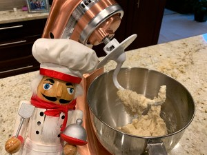 Copper colored KitchenAid mixer kneading pizza dough with dough hook. There's a nutcracker who looks like a chef in the foreground.