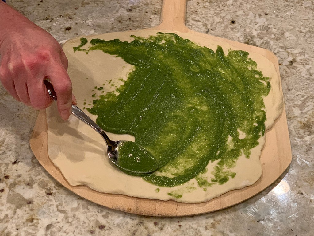 Female hand spreading bright green nettle pesto on a rolled out pizza dough with a metal spoon. Dough is on wooden pizza peel and that's on a granite surface.
