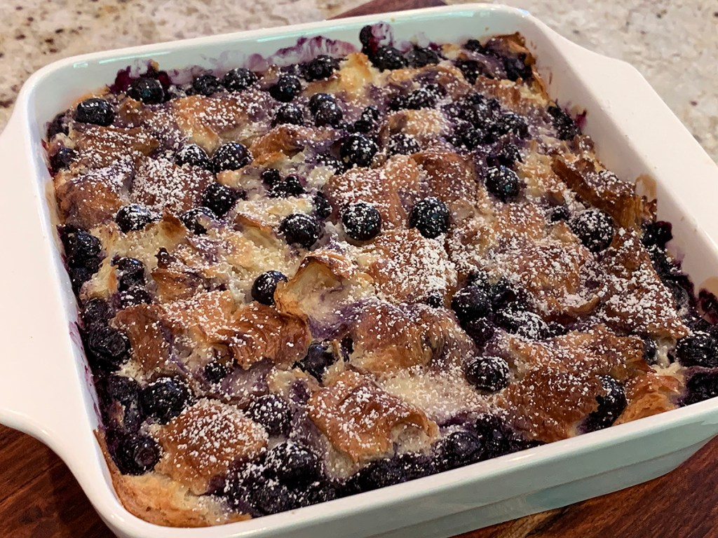 Baked blueberry & cream cheese croissant puff dusted with powder sugar in a white square casserole dish.