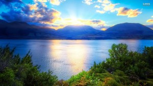 Blue mountains with sun rising behind and lake in front