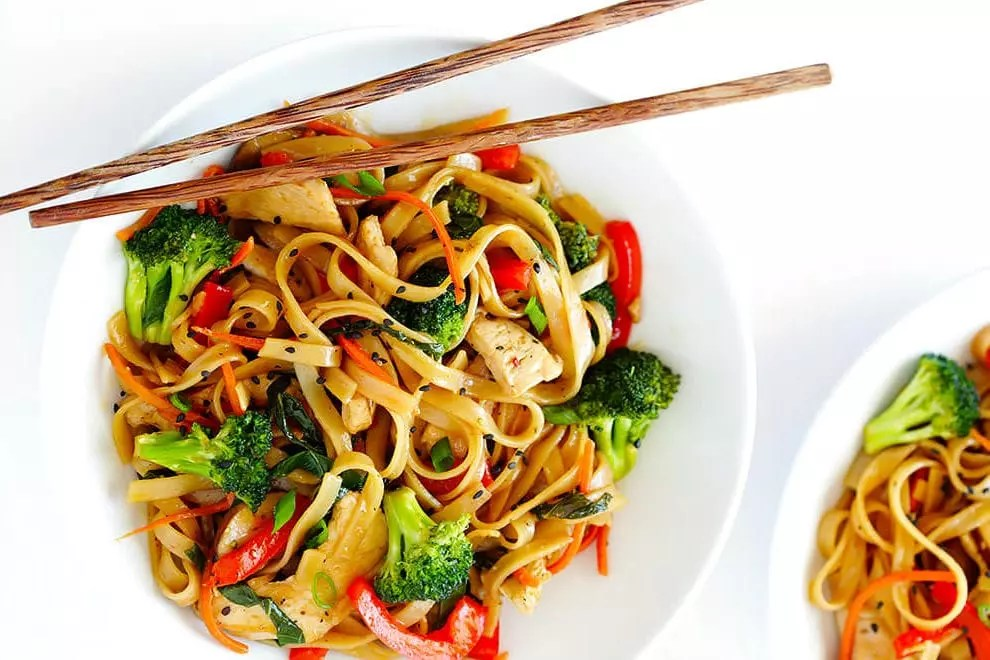 closeup of chicken noodle stir fry with broccoli, chicken and red pepper