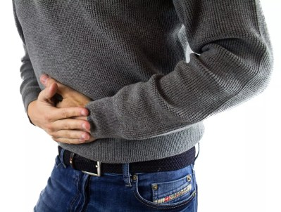 Closeup of mans torso holding stomach pain caused by Irritable Bowel Syndrome