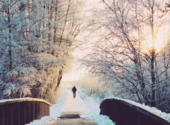 Man walking outside in the snow on a path over a bridge taking time for selfcare to survive the holidays