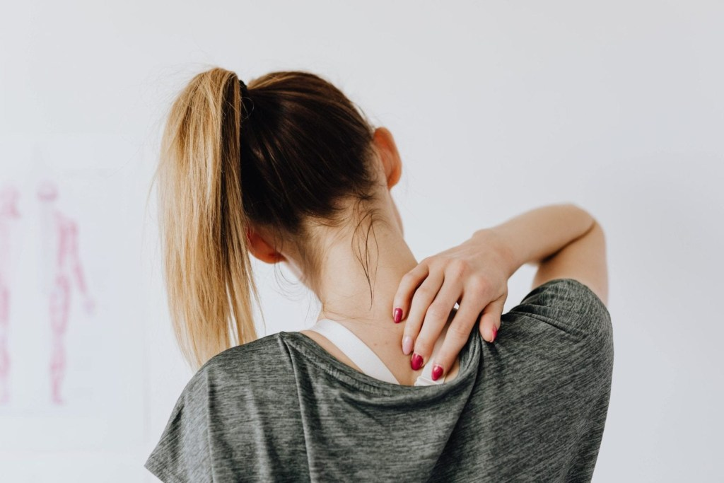 Woman pressing on a trigger point on her back, highlighting massage therapy as a treatment for headache relief