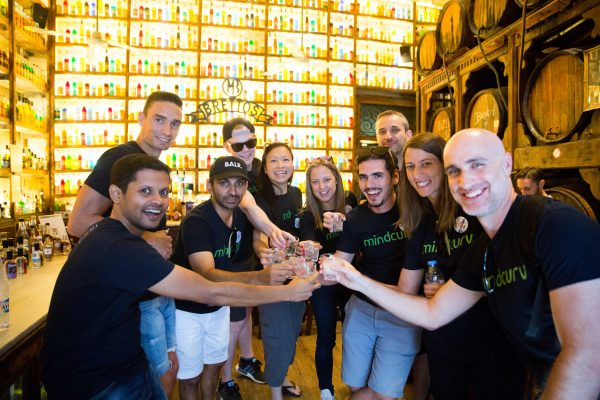 Mindcurv members toasting inside a bar in Old Town Athens