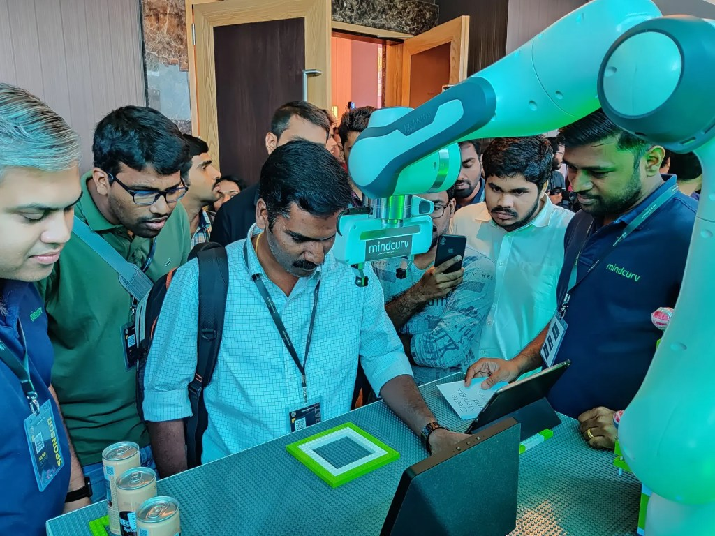 Visitors of AWS Cochin event at Mindcurv's booth surrounding the panda showcase.