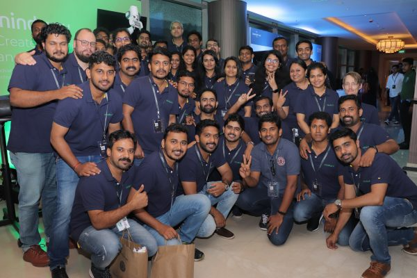 Group shot of mindcurv members gathered in front of the booth at the AWS Cochin event