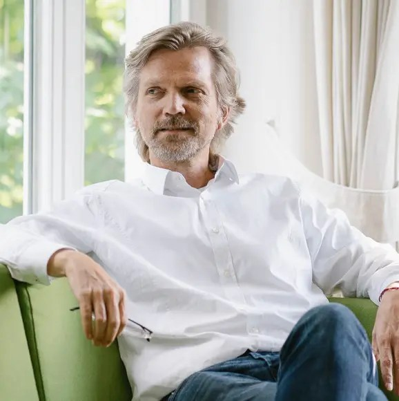 Vincent De Jong, Director sitting on green sofa, holding reading glasses at Mindcurv Essen office