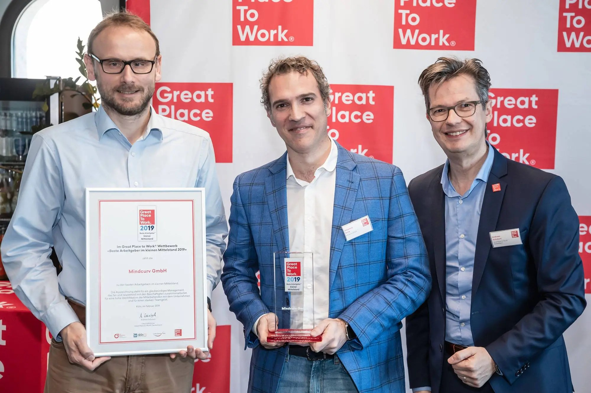 Ulf Gabel and Nazareno Avila holding certificate and award provided by Great Place to Work representative for Mindcurv Germany