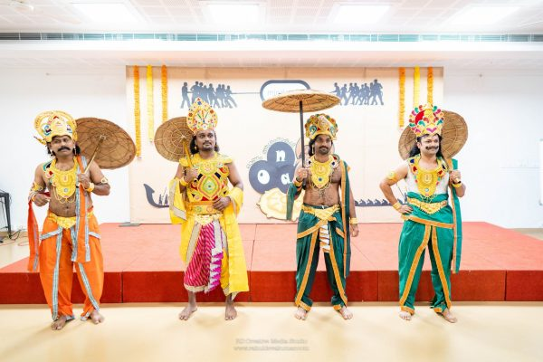Four Mindcurv male members dressed in traditional outfits in front of a stage to celebrate Onam