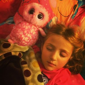 a child sleeping with a stuffed owl
