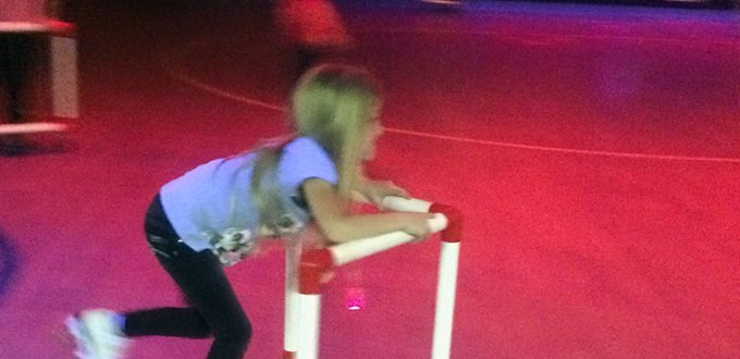 Blonde child skating with assistance in a purple and red rink.