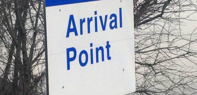 "A blue and white sign that read ""Arrival Point"" placed next to a river with dormant trees in the background."