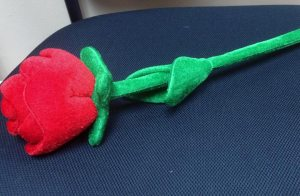 A synthetic, red rose lying upon a chair.