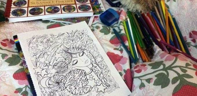 A coloring book lying upon a bed with colored-pencils and a mandala coloring book in the background.