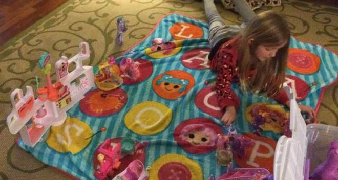 Blonde girl playing with her toys spread out upon a colorful blanket.