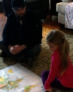 A bearded man in a black coat sitting with a blonde child looking at a map of the world.