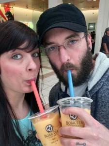 A man in a black hat and beautiful brunette woman drinking yellow Boba tea together in a mall.