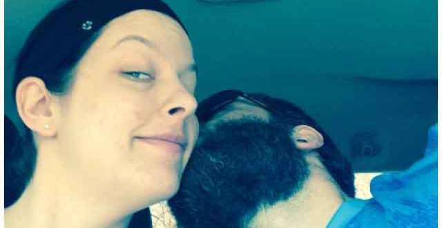 Bearded man kissing woman inside truck cab.