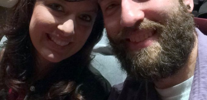 Bearded man with short hair and brunette woman with heads together smiling.