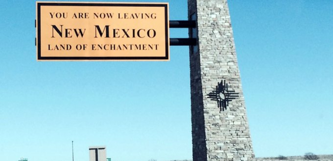 "An orange and brown sign, reading ""leaving New Mexico,"" set against a clear blue sky."