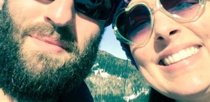 Happy couple in full ski apparel and sunglasses riding up a ski lift. Close up of faces.