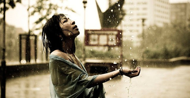 Image of woman catching rain in her hands.