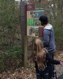 A man wearing a black hat and blue sweater looking at a nature sign with a young blonde girl, looking intently on.