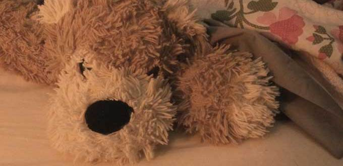 A stuffed dog with a black nose laying on a bed with a flowered bedspread.