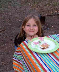 Blonde girl grinning with a half-eaten Smore on the plate.