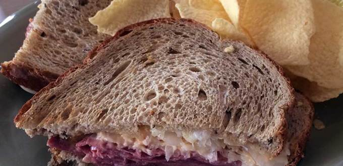 A Reuben sandwich with baked chips in the background.