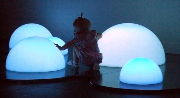 A small child investigating glowing blue orbs on the ground.