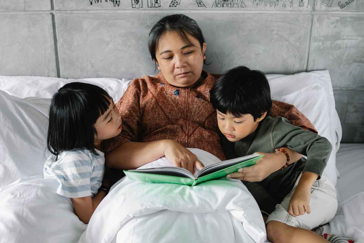 senor ethnic woman reading fairy tale to cute grandchildren on bed