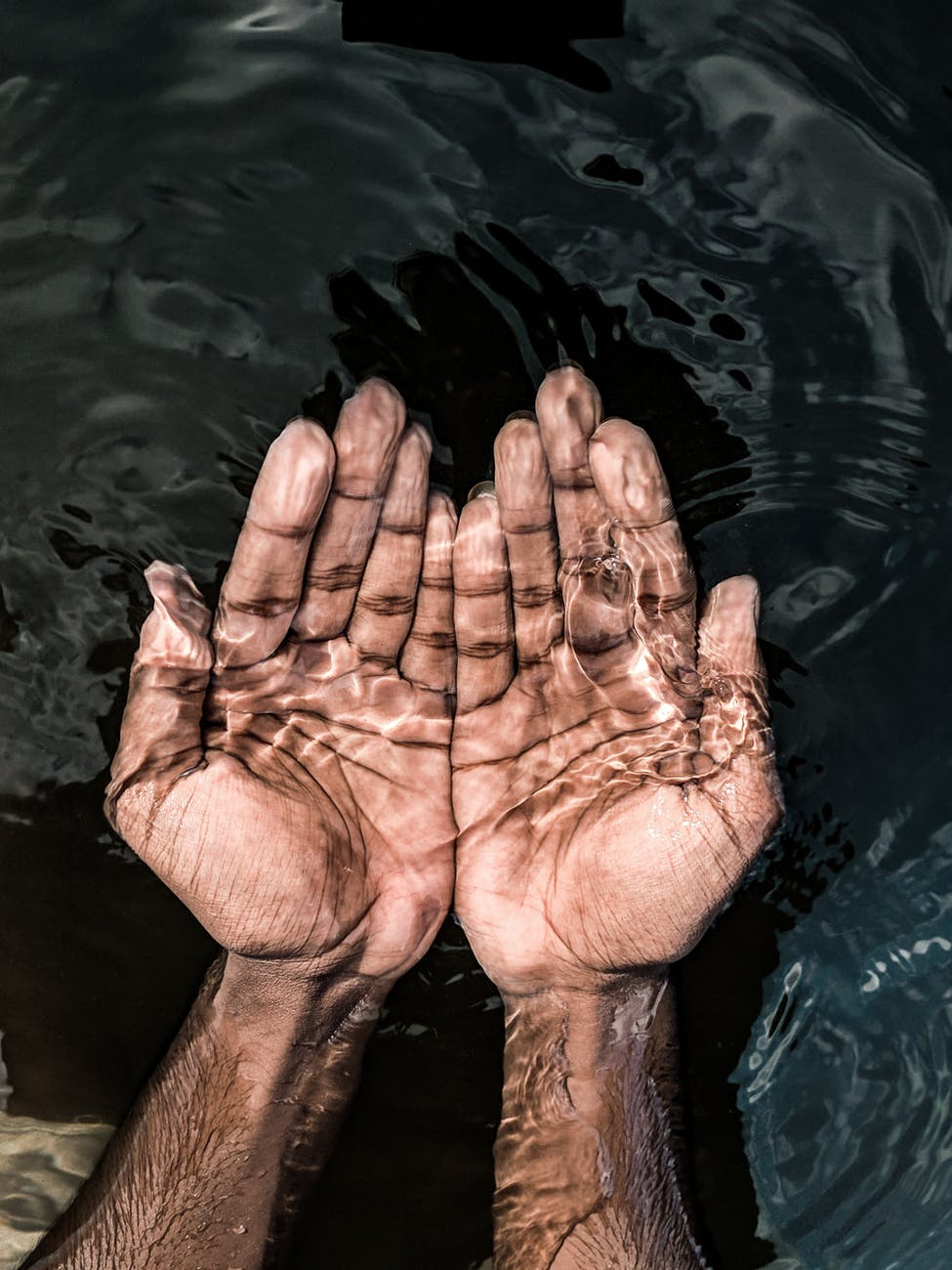 crop man with hands under transparent water
