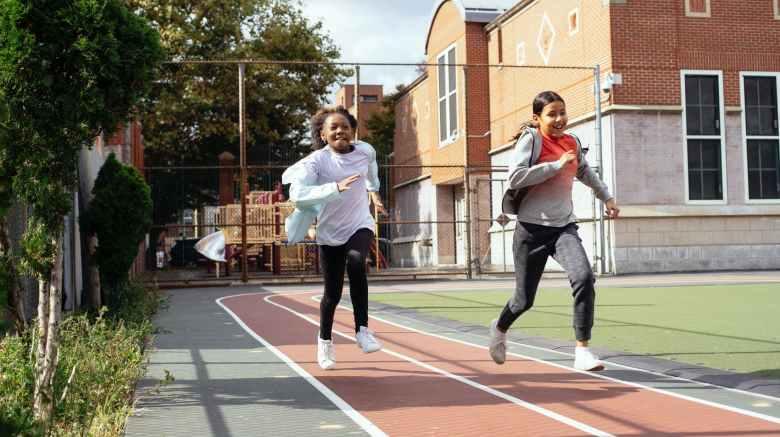 happy multiethnic girlfriends running fast on stadium