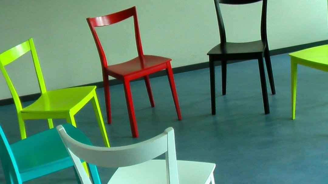 Six colorful wooden chairs positioned in a circle
