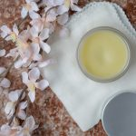 DIY Cleansing Balm on counter with flowers