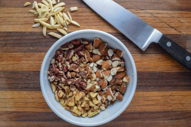 Nuts for granola in bowl with knife