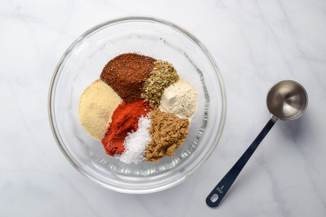 taco seasoning spices in a glass bowl with measuring spoon