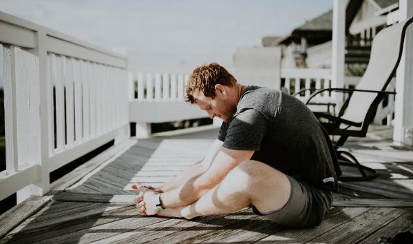 man stting on balcony stretching legs