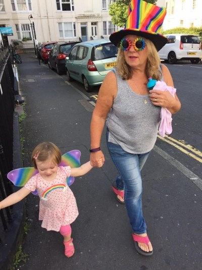dawn wearing a rainbow top hat and sunglasses walking down the road with ella ray who is wearing rainbow butterfly wings