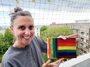white woman, wearing a grey top, holding a pride flag she created.