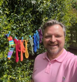 white man standing in front of colourful socks that resemble pride colours, he's wearing a pink shirt and has silver hair
