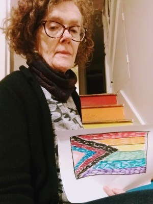 white woman holding a pride flag that she drew, sitting by the stairs