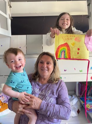white woman, with two babies, one of them is holding a rainbow drawing