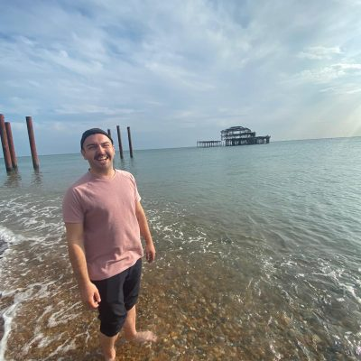A person standing in the shallow ocean, wearinga pink shirt and grey shorts, smiling into the camera
