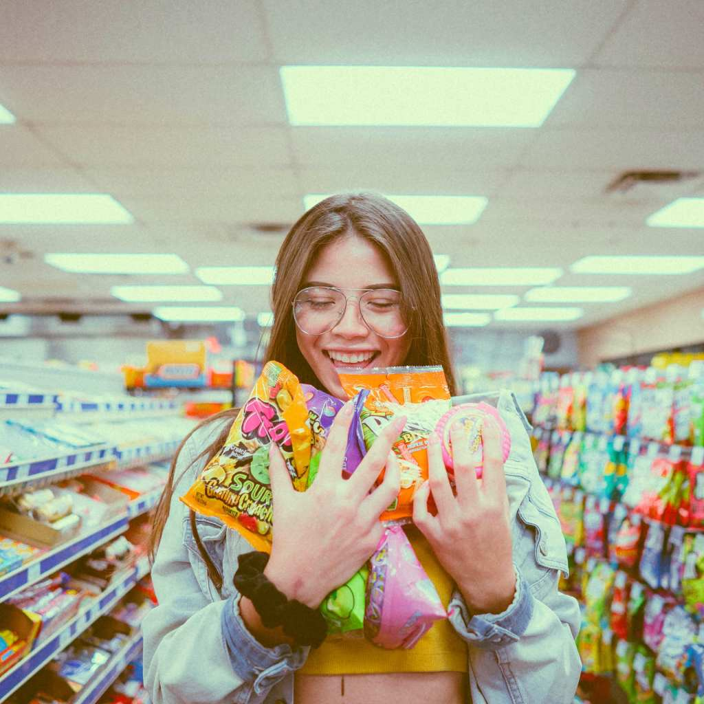 A girl in a shopping aisle with an armfull of junk food.