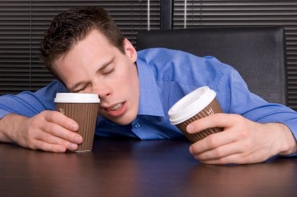Man in blue shirt with a coffee cup in each hand  sleeping on one of the cups on a brown desk