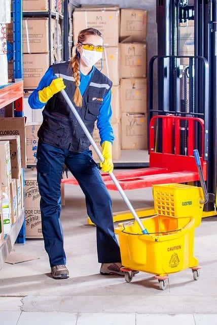 A woman in a uniform with cleaning supplies