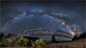 Milky Way arches over a panorama of the South Fork Bridge railroad trestle over the Main Fork Eel River, California.